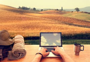 Digital nomads are people who can work from anywhere using a laptop and an internet connection: from an hillside italian town in Tuscany a young male traveller is typing on his laptop computer on a wooden table, with a travel backpack and a mug with coffee. On the background a beautiful panorama of hills covered by corn fields and trees at sunset. Laptop display reflects sky with clouds.